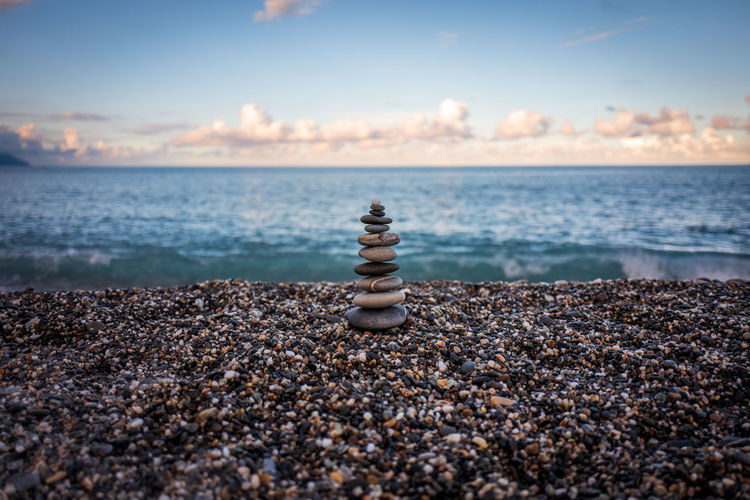 Stack of pebble stones on beach against sky
