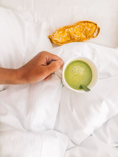 Cropped hand holding matcha tea on bed