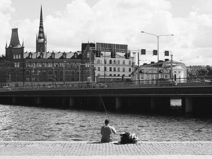 Rear View Of Man Fishing By Lake Malaren Against Riddarholm Church