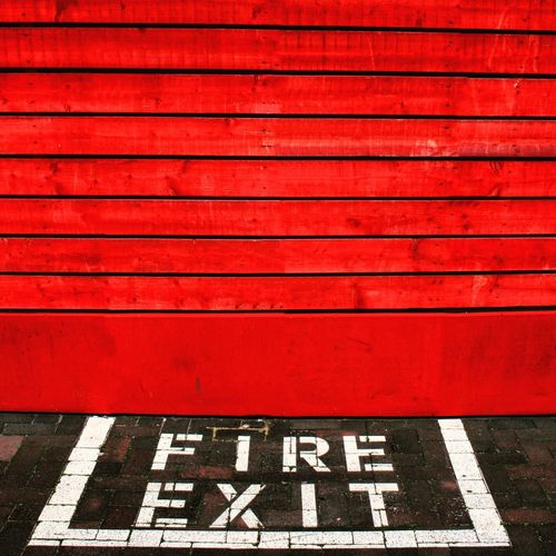 High Angle View Of Fire Exit Sign By Red Door