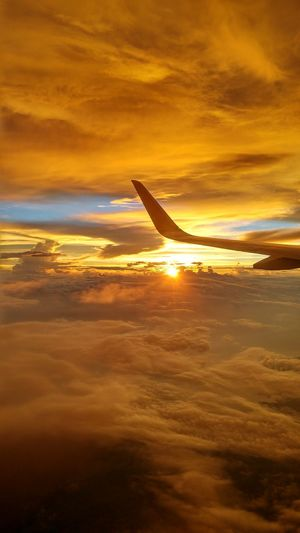 Airplane flying over sea during sunset