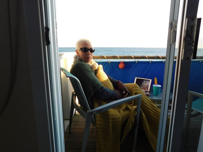 Portrait of mature woman wearing sunglasses while sitting on balcony by sea