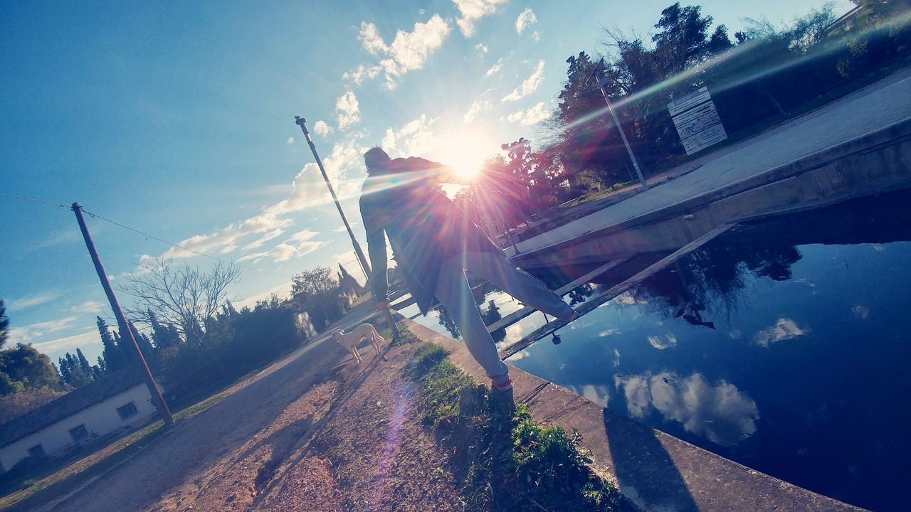 sky, cloud - sky, lens flare, sunlight, transportation, road, outdoors, day, built structure, no people, nature, tree, building exterior, water, architecture