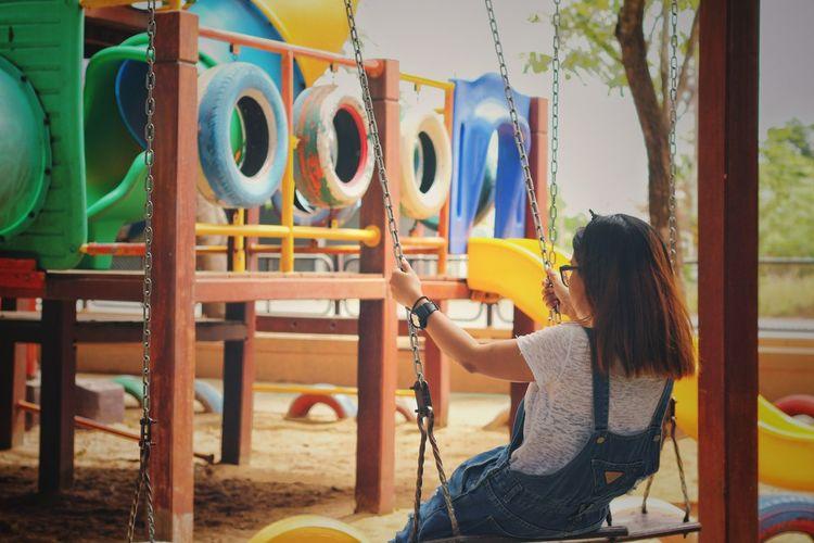 Woman sitting on slide at playground