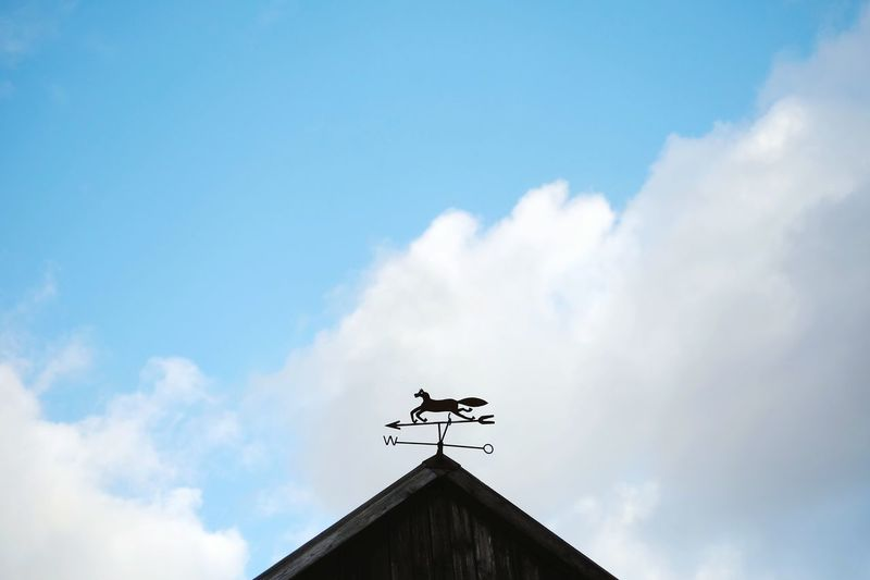Low Angle View Of Weather Vane On House Pediment Against Sky