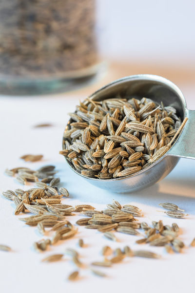 Cumin seeds spilled from a measuring spoon Close Up Cuisine Culinary Cumin Flavor Food Herb Ingredient Isolated Measuring Spoon Seasoning Seeds Spice Teaspoon
