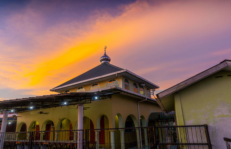 Low angle view of traditional building against sky during sunset