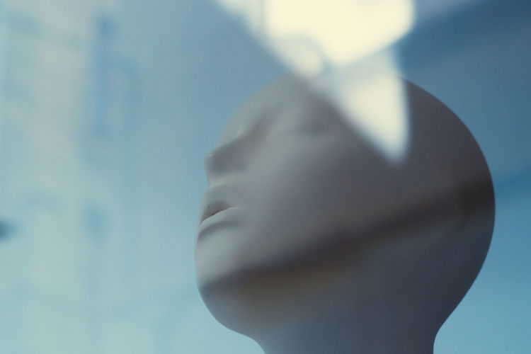 Low angle view of mannequin seen through glass