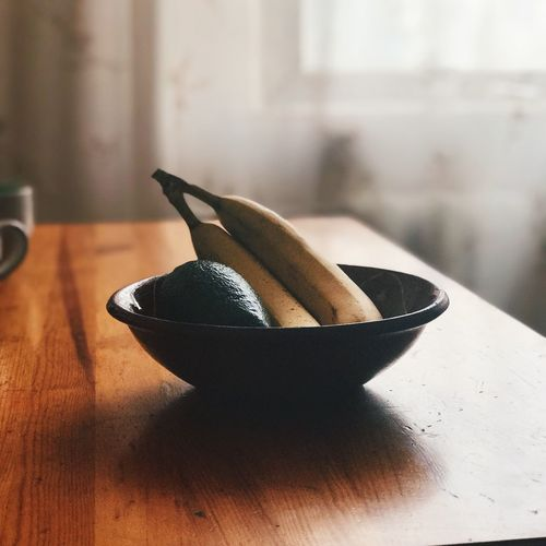 Close-up of bananas and avocado in bowl on table