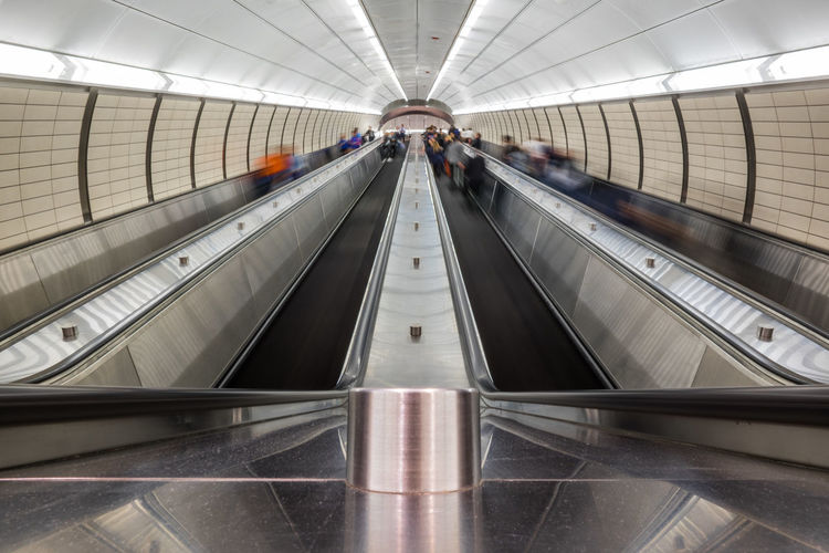 Blurred Motion Of People On Escalators In Subway Station