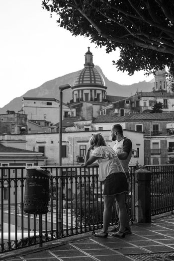 Rear view of couple standing against railing in city