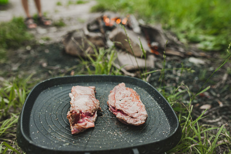 Meat steak is fried in grill pan on gas stove in open air on grass. cooking meal at picnic. healthy