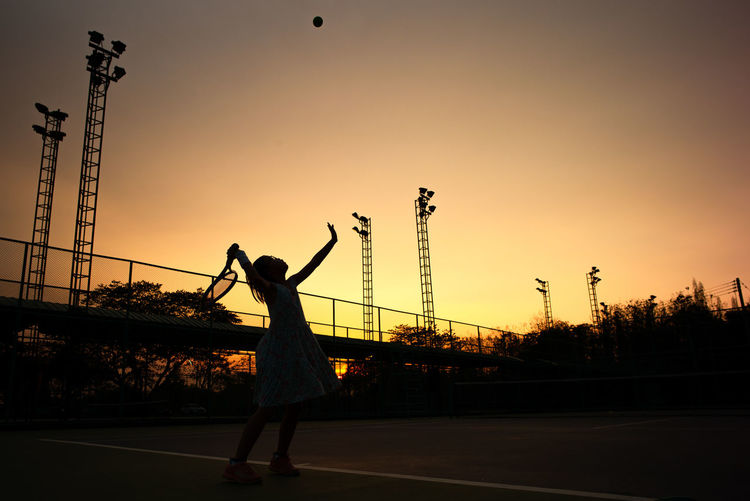 Silhouette portrait Asian girl plays tennis at the outdoor court with sunset orange sky in background Sunset Sky Silhouette Lifestyles Sport Tennis Healthy Eating Girl Portrait Leisure Activity Orange Color Sunrise Twilight Spotlight Structure Tower Fence Metal Close-up Shadow Light And Shadow Arms Raised Child Standing Service Served Plant Training Practicing Tournament Abstract Exercise Workout Full Frame Fun