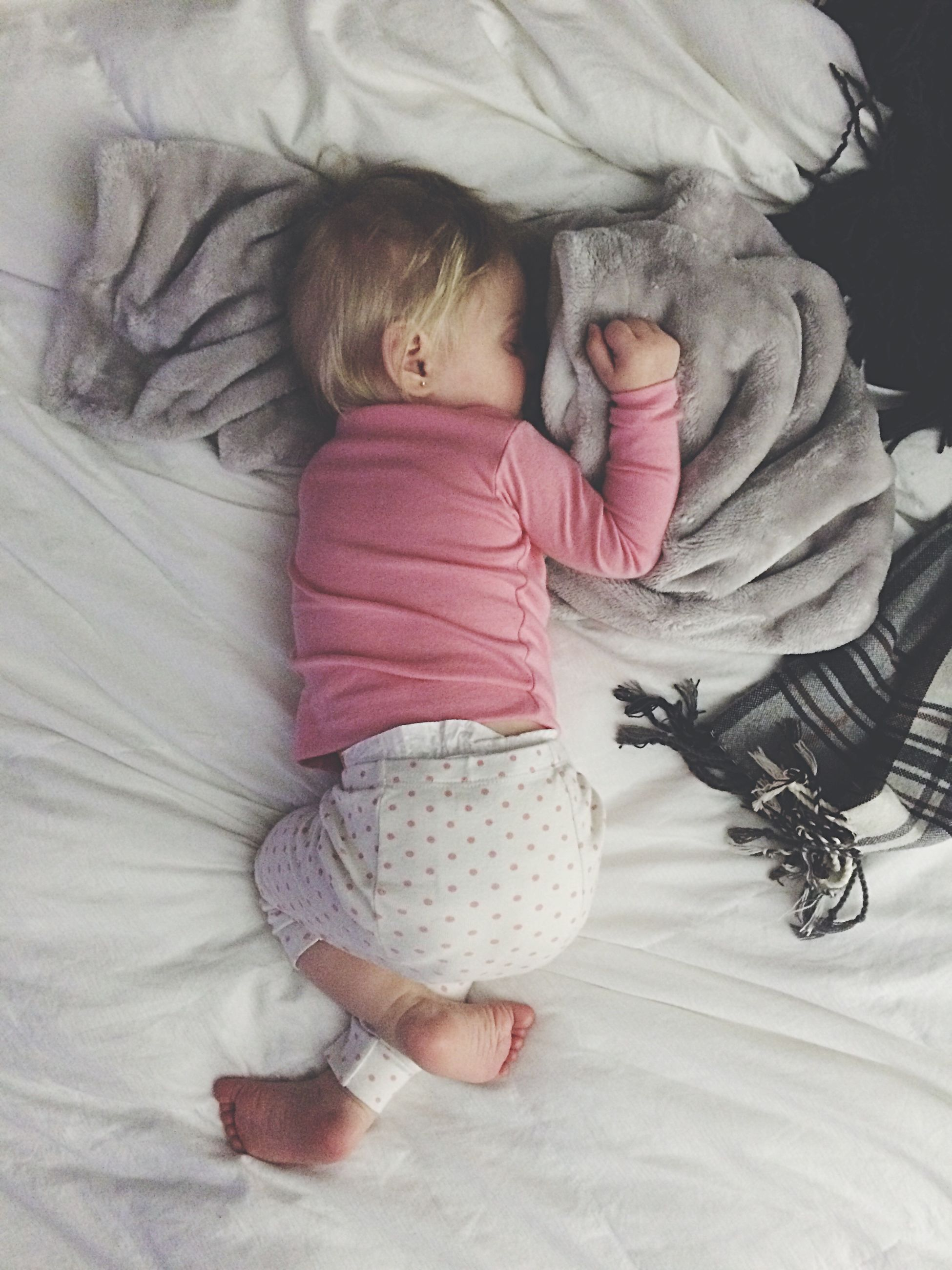 indoors, bed, childhood, lifestyles, holding, baby, relaxation, leisure activity, babyhood, home interior, unknown gender, sleeping, high angle view, toddler, casual clothing, toy, pillow, togetherness
