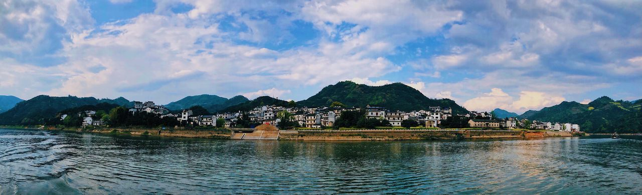 Panoramic view of buildings by mountains against sky