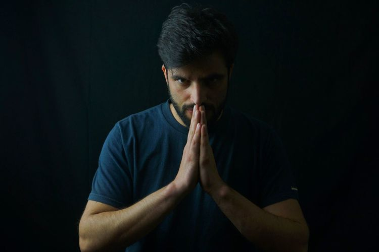 Portrait of man with hands clasped against black background
