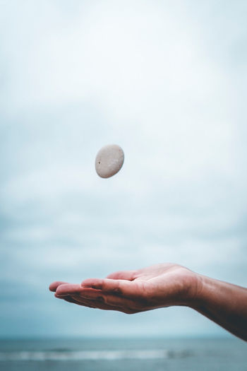 Close-up of hand catching stone against sea and sky