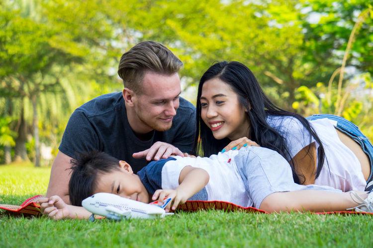 Happy family lying on grassy field at park