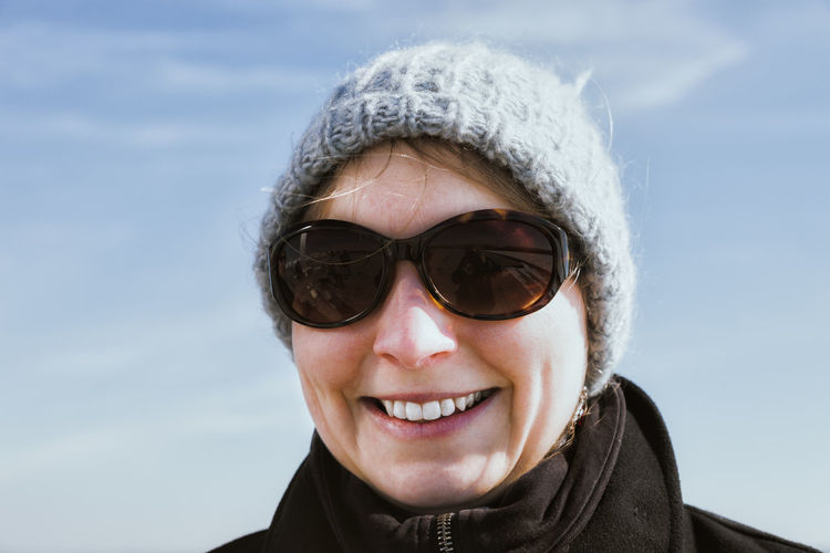 Portrait of smiling woman wearing sunglasses against sky