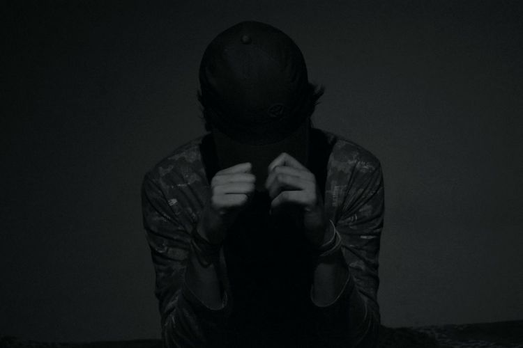 Close-up of man covering face over black background