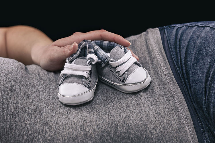 Midsection of pregnant woman holding small shoes