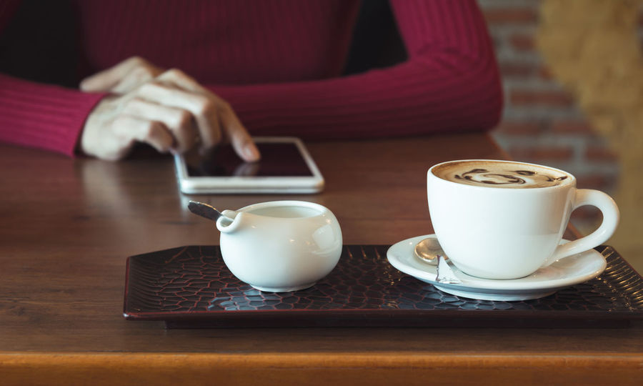 Female using a tablet with coffee cup on wooden table. Mug Cup Drink Coffee Refreshment Coffee Cup Coffee - Drink Food And Drink Table Crockery Saucer Indoors  Hand One Person Human Hand Hot Drink Adult Tea Eating Utensil Freshness Tea Cup Non-alcoholic Beverage Tray
