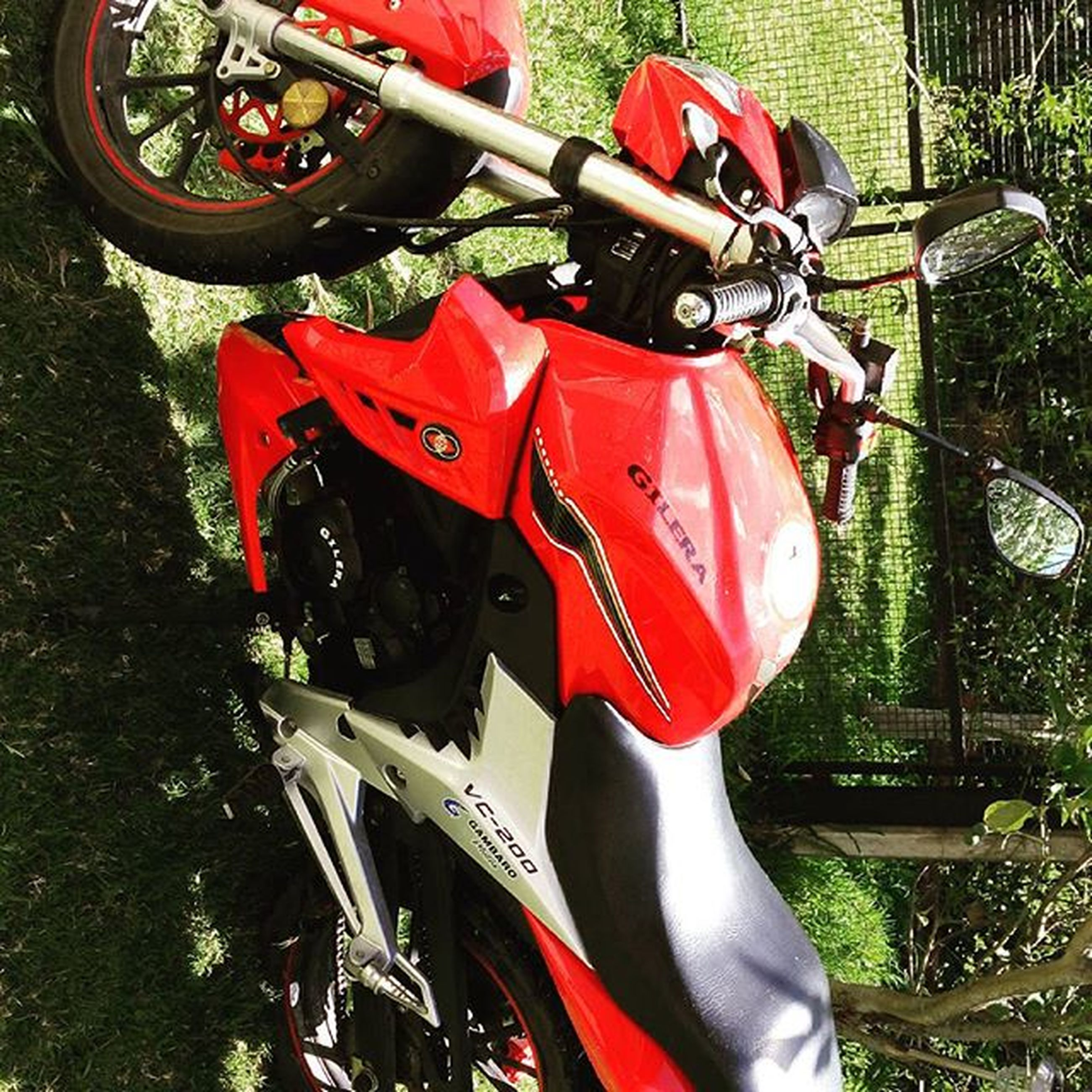 land vehicle, transportation, mode of transport, car, red, high angle view, outdoors, wheel, day, stationary, bicycle, sunlight, grass, close-up, no people, part of, motorcycle, travel, parking, low section
