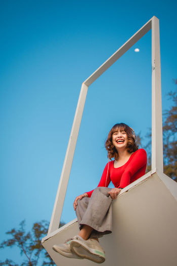 Portrait of smiling young woman sitting against blue sky