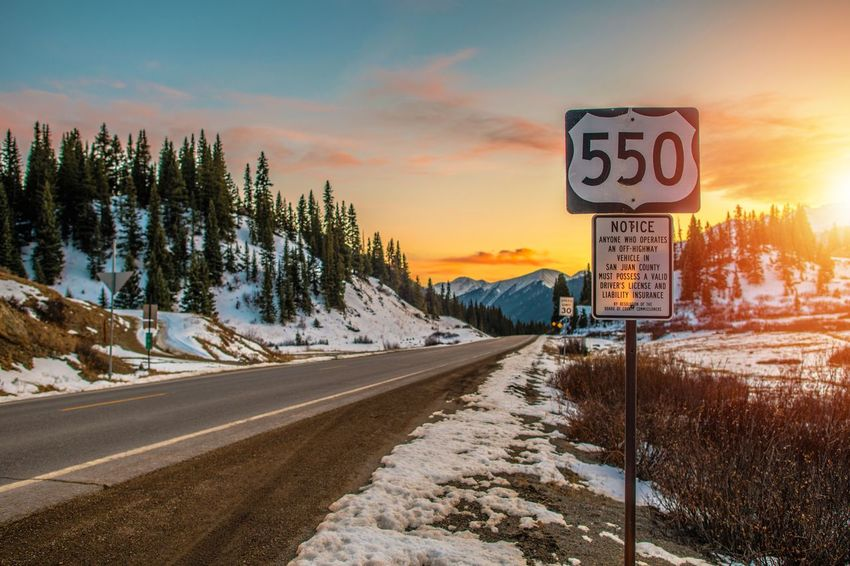 Colorado Highway 550. Famous Million Dollars Highway Near Durango, Colorado, United States. San Juan County. USA Beauty In Nature Cold Temperature Communication Day Highway 550 Million Dollar Highway Nature No People Outdoors Road Road Sign Scenics Sky Snow Speed Limit Sign Sunset Text The Way Forward Transportation Tree Winter