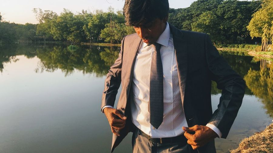 Man wearing suit standing by lake