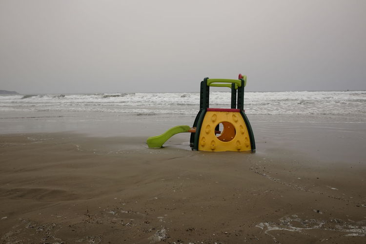 deserted beach game in winter Water Sea Beach Land Sky Horizon Over Water Horizon Scenics - Nature Nature Tranquility No People Tranquil Scene Yellow Day Sand Non-urban Scene Outdoors Toy Floating On Water Game Equipment