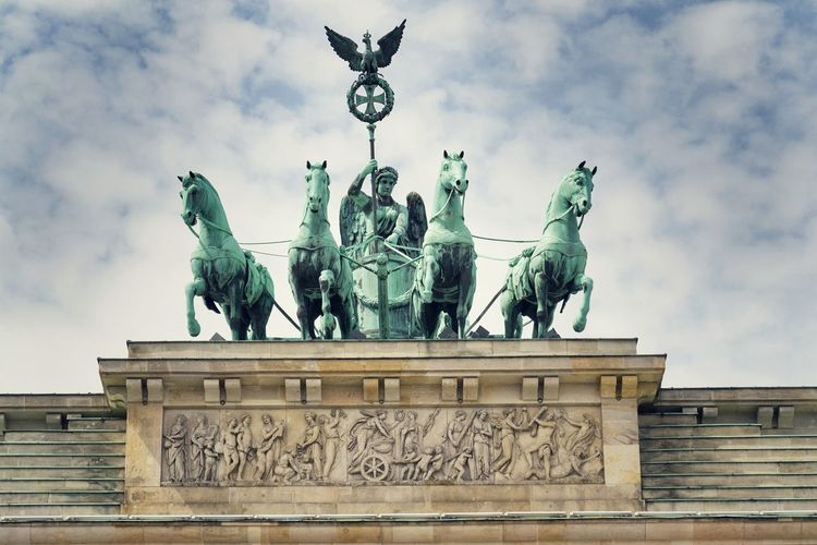 Quadriga on Brandenburg Gate, dramatic cloudy sky background, Berlin, Germany Brandenburger Tor Brandenburg Gate Quadriga Berlin Germany Dramatic Cloudy Sky Blue Background Landmark Statue Symbol National Monument Pariser Platz Neoclassical Architecture City Travel Europe Famous Capital Urban Tourism Old History Column View Culture Sightseeing Historic Wall Place Cityscape Scene Street Horse Center Sculpture Destination Square Exterior Copy Space Horizontal