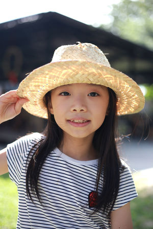 Cute little Asian girl wearing a hat and playing outside in the summer sun Casual Clothing Child Childhood Clothing Females Focus On Foreground Front View Girls Hairstyle Hat Innocence Leisure Activity Lifestyles Looking At Camera One Person Outdoors Portrait Real People Smiling Standing Sun Hat Waist Up