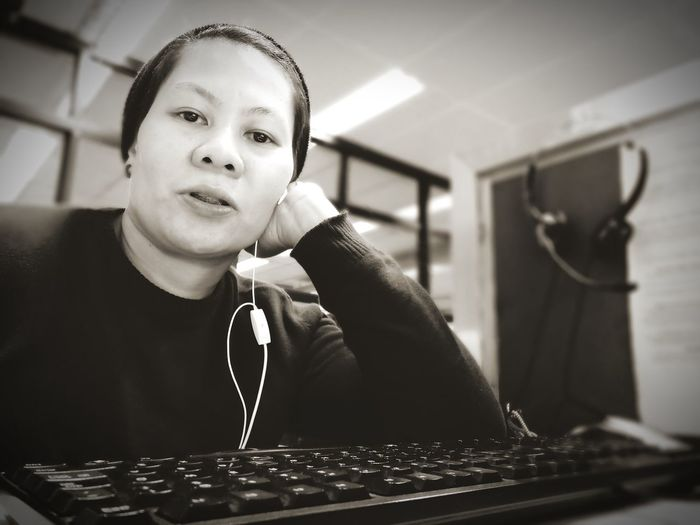 Portrait Of Woman With In-Ear Headphones Sitting With Computer Keyboard