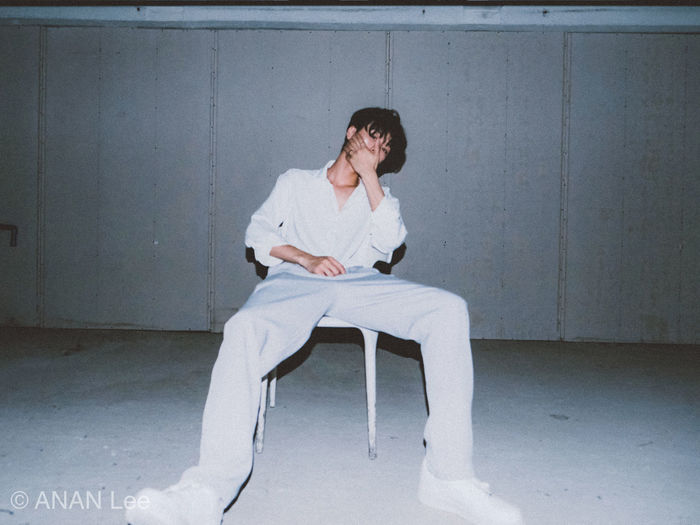 Young man sitting on chair against wall