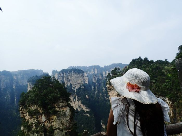 Rear view of woman looking at rock formations against sky