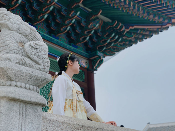 Low angle view of woman looking away while standing at temple