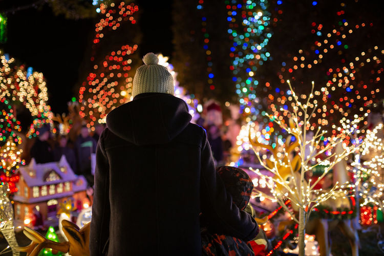 Rear view of people standing against illuminated christmas lights at night