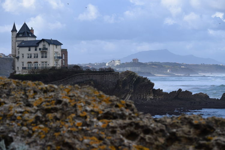 Buildings on hill by sea against cloudy sky