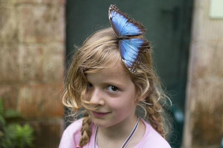 Little girl with a butterfly on her hair Females Animal Themes Beauty In Nature Butterfly Caucasian Ethnicity Child Childhood Cute Day Fauna Focus On Foreground Girls Hair Hairstyle Headshot Innocence Insect Looking At Camera Portrait Waist Up Wildlife