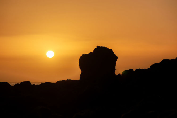 Silhouette rock formation against sky during sunset