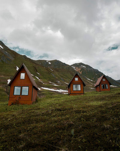 Red chalets in a line in the lush green alaskan mountains
