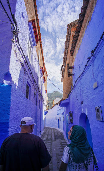 """""""The Blue City"""" We travelled from Sevilla to Tarifa, then took a ferry to Tangier, then a taxi to Chefchaouen, Morocco. EyeEmNewHere a new beginning Chefchaouen Morocco Beauty Blue City Blue Medina Street Warm Clothing Incidental People Alley People Building Architecture Building Exterior City Real People Lifestyles Day Walking Group Of People Digital Nomad Built Structure Rear View Women Adult Nature Residential District Sky Men"""