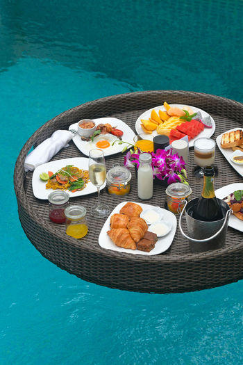 High angle view of breakfast served on table by swimming pool