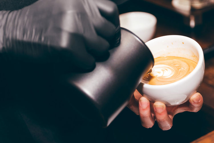 Cropped Image Of Barista Adding Milk In Coffee At Shop