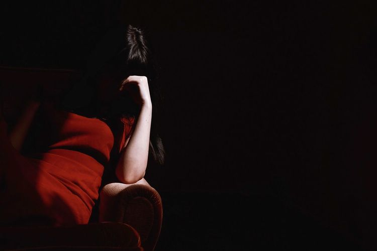 Woman sitting on sofa with head in his hand