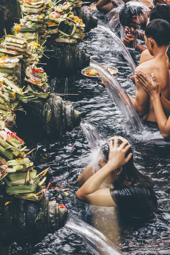 High angle view of people swimming in water at temple
