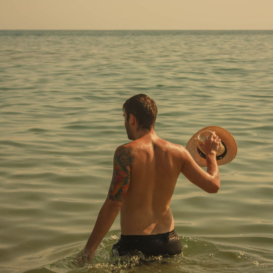 Rear view of shirtless man standing in sea during sunset