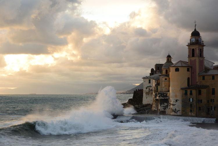 Sea waves splashing on shore against buildings