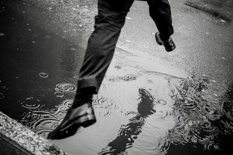 Low section of man jumping over puddle on road during rainy season